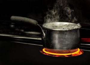 Horizontal shot of a boiling pot of water on a stovetop with a glowing red element.