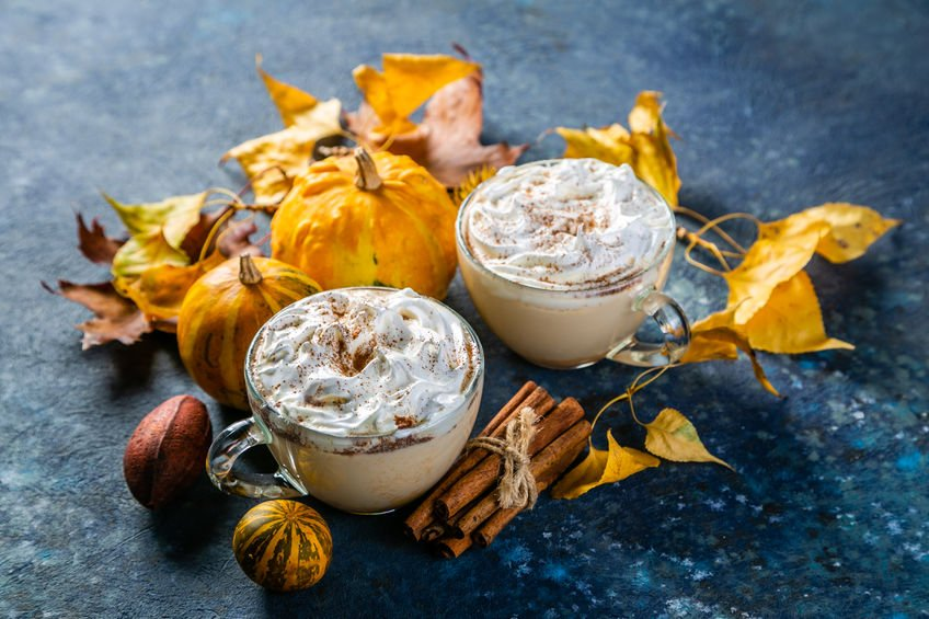 Pumpkin spice latte in glass cups on concrete blue background, copy space