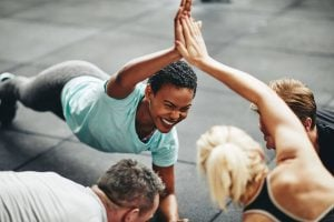 Two fit women giving high five during exercise routine