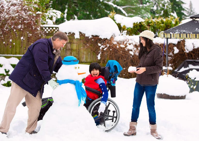 asian family with child in wheelchair making snowman