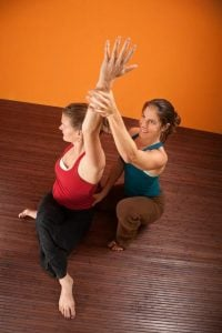 yoga instructor helping student | Activated You